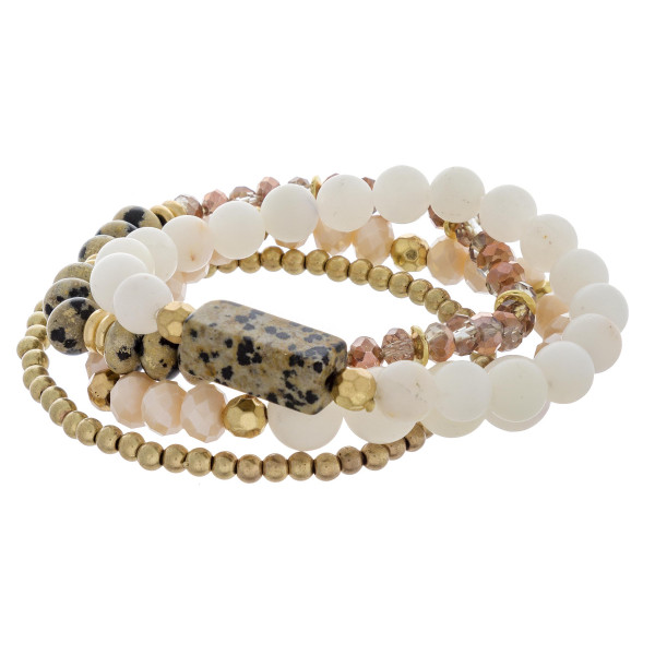 "Bracelet set featuring four stretch bracelets with a natural stone inspired focal, faceted and iridescent beaded details with gold accents. Approximately 3"" in diameter unstetched. Fits up to a 6"" wrist."