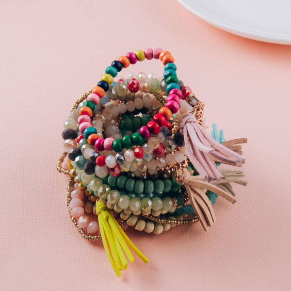 """Beaded bracelet set featuring four stretch bracelet with wood and faceted bead details and a faux leather tassel accent. Approximately 3"""" in diameter unstretched. Fits up to a 6"""" wrist."""