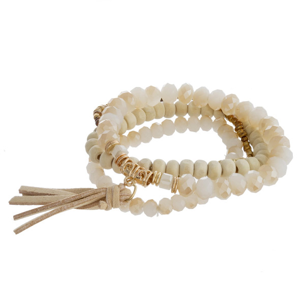 "Beaded bracelet set featuring four stretch bracelet with wood and faceted bead details and a faux leather tassel accent. Approximately 3"" in diameter unstretched. Fits up to a 6"" wrist."