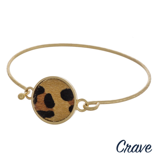 """Gold metal bangle bracelet featuring a leopard print faux leather focal. Approximately 2.5"""" in diameter. Fits up to a 5"""" wrist."""