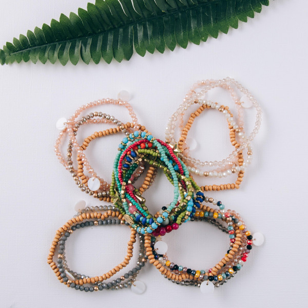 """Bracelet set featuring eight stretch bracelets with bolo bead details and gold metal charms. Approximately 3"""" in diameter unstretched. Fits up to a 6"""" wrist."""