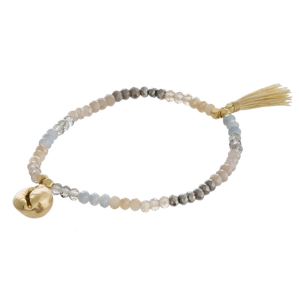 "Dainty beaded stretch bracelet featuring faceted bead details with a gold puka shell and tassel accent. Approximately 3"" in diameter unstretched. Fits up to a 6"" wrist."