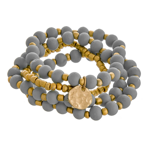 """Bracelet set featuring five wooden bead stretch bracelets with gold metal accents. Approximately 3"""" in diameter unstretched. Fits up to a 6"""" wrist."""