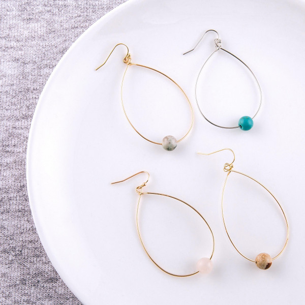 "Dainty metal teardrop earrings featuring a natural stone inspired bead accent. Approximately 2"" in length."