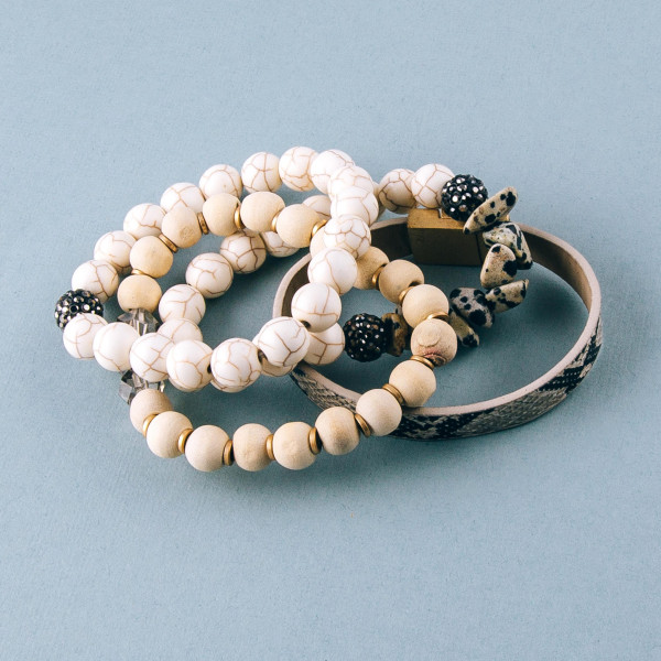 """Natural stone beaded stretch bracelet set featuring wood and iridescent bead details with a faux leather snakeskin strand with a magnetic closure. Approximately 3"""" in diameter. Fits up to a 6"""" wrist."""