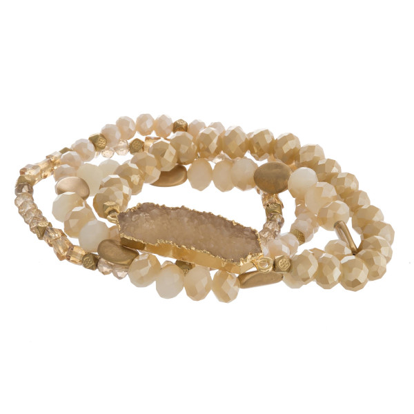 """Semi precious beaded stretch bracelet featuring a druxy bar focal with faceted and gold bead details. Approximately 3"""" in diameter. Fits up to a 6"""" wrist."""