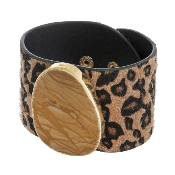 "Faux fur leather leopard print bracelet featuring a natural stone focal with an adjustable button snap closure. Approximately 3"" in diameter and 2"" wide."