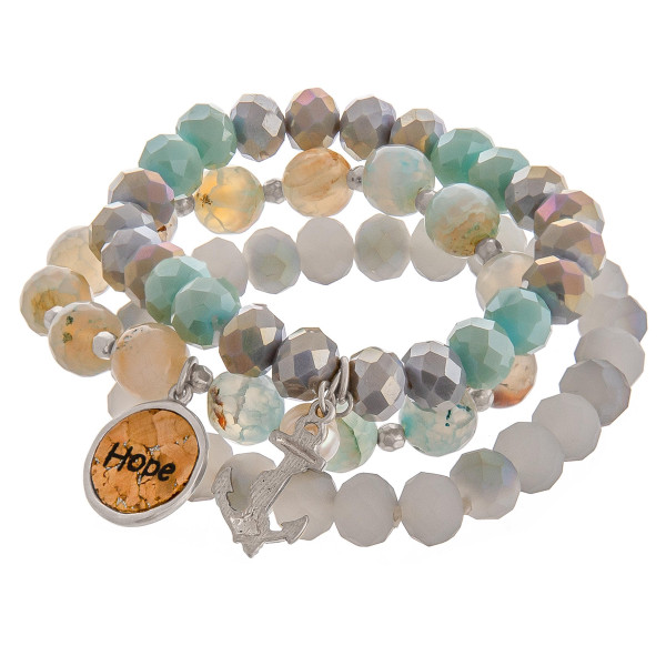 """Smokey Mint faceted acrylic beaded stretch bracelet set featuring a cork """"Hope"""" charm with a silver anchor and pearl accent. Approximately 3"""" in diameter unstretched. Fits up to a 6"""" wrist."""