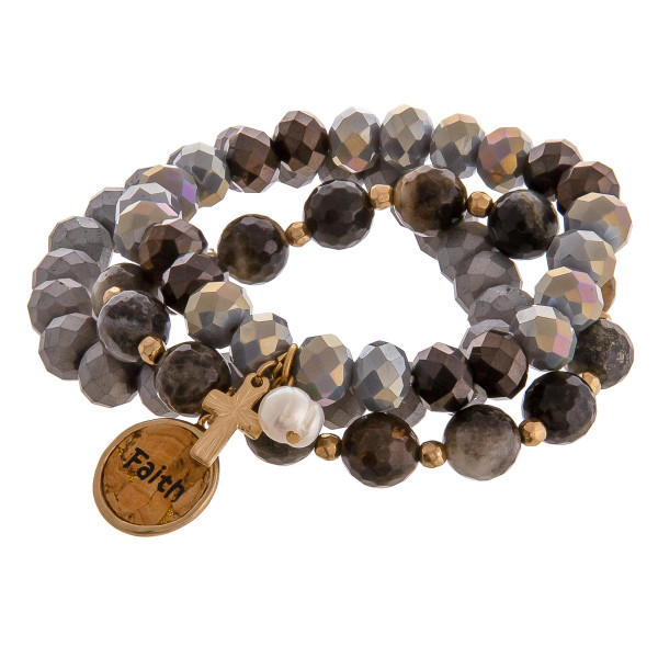 """Smokey Grey faceted acrylic beaded stretch bracelet set featuring a cork """"Faith"""" charm with a gold cross and pearl accent. Approximately 3"""" in diameter unstretched. Fits up to a 6"""" wrist."""