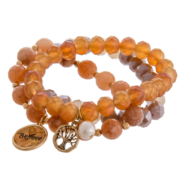 """Smokey Brown faceted acrylic beaded stretch bracelet set featuring a cork """"Believe"""" charm with a gold tree of life charm and pearl accent. Approximately 3"""" in diameter unstretched. Fits up to a 6"""" wrist."""