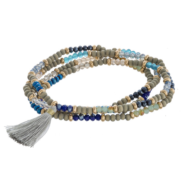 "Wood, iridescent and faceted beaded stretch wrap bracelet featuring gold accents and a tassel detail. Approximately 3"" in diameter unstretched. Fits up to a 6"" wrist."