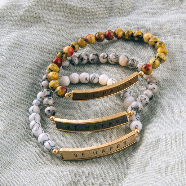 """Natural stone beaded stretch bracelet featuring a faux leather focal with """"Be Happy"""" engraved details. Approximately 3"""" in diameter unstretched. Fits up to a 6"""" wrist."""