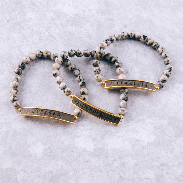 """Natural stone beaded stretch bracelet featuring a faux leather focal with """"Faith, Hope, Love"""" engraved details. Approximately 3"""" in diameter unstretched. Fits up to a 6"""" wrist."""