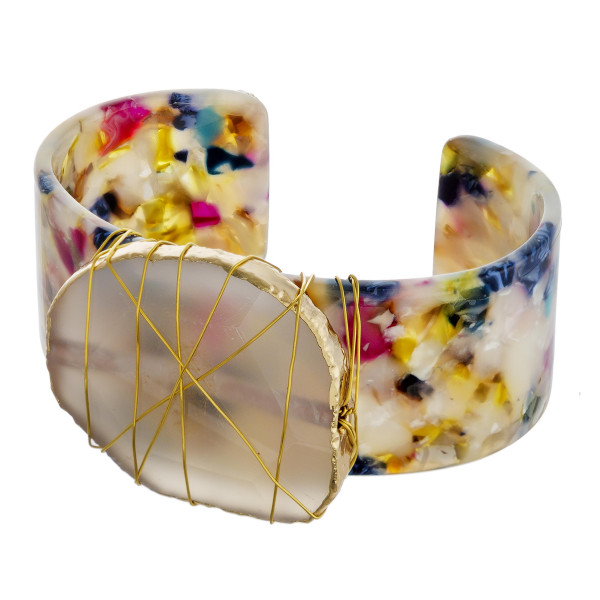 "Resin cuff bracelet featuring a quartz inspired stone with wire wrapped details. Approximately 3"" in diameter. Fits up to a 6"" wrist."