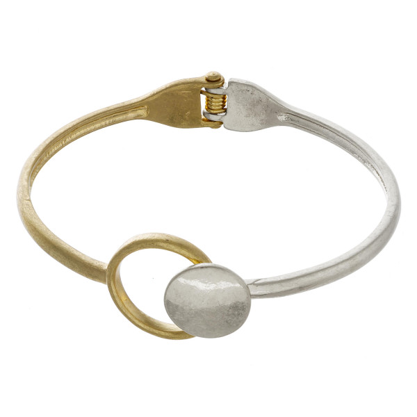 """Two tone hinged bangle bracelet featuring a circular focal. Approximately 3"""" in diameter."""