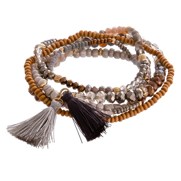 """Wood and faceted beaded stretch bracelet set with tassels. Approximately 3"""" in diameter. Fits up to a 6"""" wrist."""