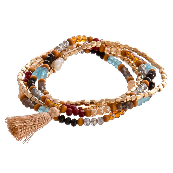 """Wood and faceted beaded stretch bracelet set with pearl and tassel accents. Approximately 3"""" in diameter unstretched. Fits up to a 6"""" wrist."""