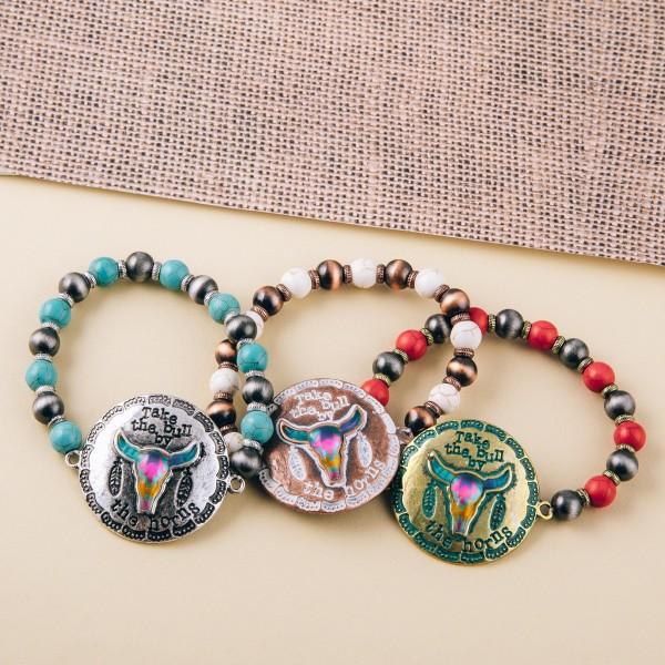"""Semi precious beaded stretch bracelet featuring patina tone focal with """"Take the bull by the horns"""" engraved details.  - Approximately 3"""" in diameter unstretched - Fits up to a 6"""" wrist"""