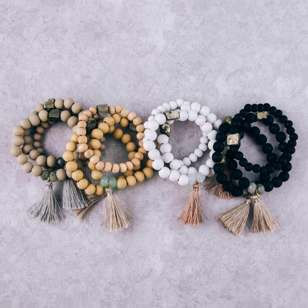 """Wood beaded stretch bracelet set of three with tassel and natural stone details. Approximately 3"""" in diameter unstretched. Fits up to a 6"""" wrist."""