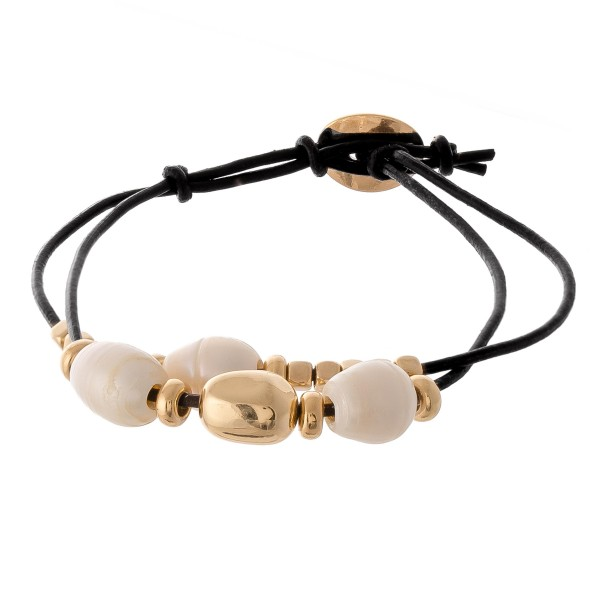 "Freshwater pearl beaded cord bracelet.  - Pull through button closure - Adjustable  - Approximately 3"" in diameter  - Fits up to a 7"" wrist"