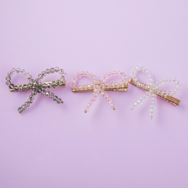 "Hair clip accessory featuring a iridescent beaded bow detail. Clip approximately 2"" in length."