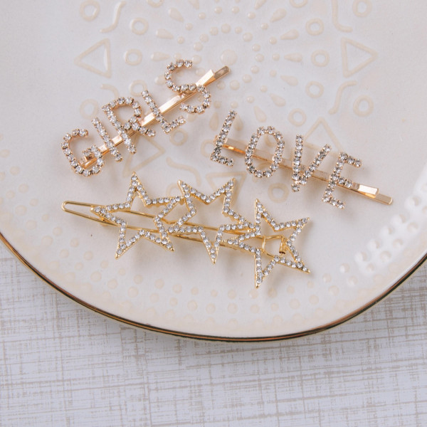 "Gold hair barrette featuring a trio star pattern with cubic zirconia details and snap closure. Approximately 2.5"" in length."