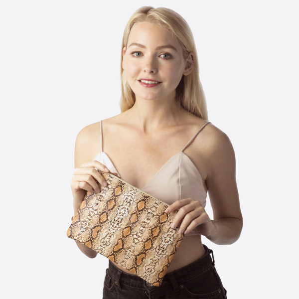 """Snakeskin clutch featuring a wristlet and a zipper closure. Approximately 7"""" x 10"""" in size.   Composition: 100% PU"""