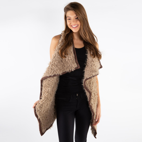 Taupe and dark brown faux fur vest with faux front pockets and a tapered front. 100% polyester. One size fits most.