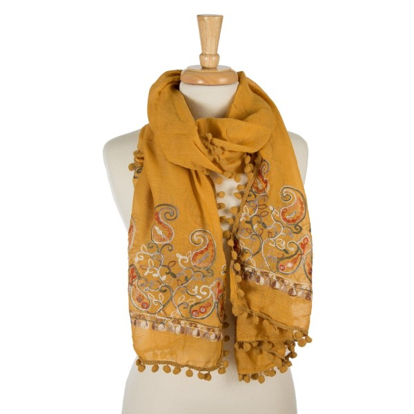 "Mustard, lightweight scarf with floral embroidery and pom poms on the outer trim. 65% polyester and 35% viscose. Measures 26"" x 70"" in size."