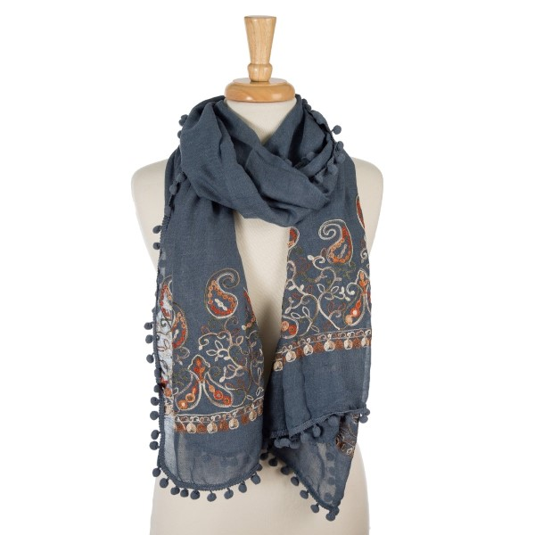 "Denim blue, lightweight scarf with floral embroidery and pom poms on the outer trim. 65% polyester and 35% viscose. Measures 26"" x 70"" in size."