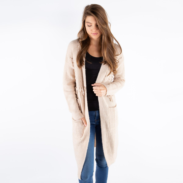 Long line cardigan with bow detail. 61% acrylic, 37% nylon, and 2% elastane.   One size fits most.