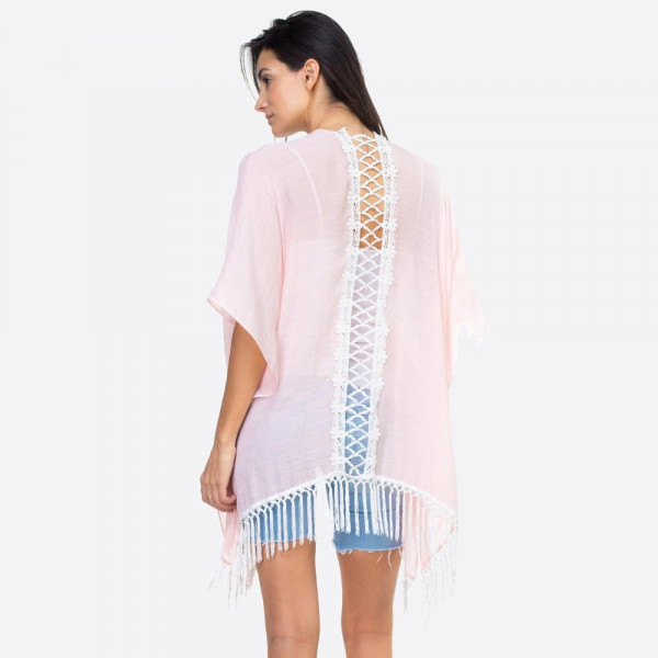 "Solid pink kimono with lace down the back and fringe detailing. One size fits most 0-14. Measures approximately 37"" x 27"" in size. 65% Polyester, 35% Cotton."