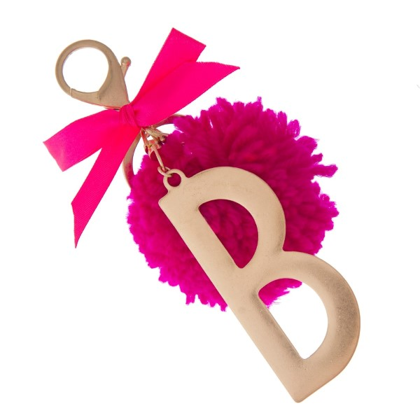 "Gold tone key chain or bag charm with a block 'B' initial pendant and fuchsia pom pom. Approximately 5.5"" in length."