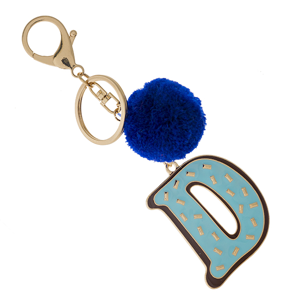 "Gold tone keychain with the ""D"" initial and a pom pom accent. Approximately 6"" in total length."