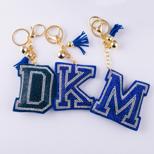 "Blue initial pillow keychain/bag charm featuring rhinestone details and a tassel accent. Initial approximately 2.5"". Approximately 6"" in length overall."