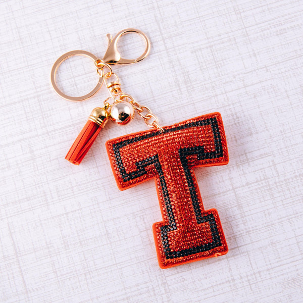 "Orange ""T"" initial pillow keychain/bag charm featuring rhinestone details and a tassel accent. Initial approximately 3"". Approximately 6"" in length overall."