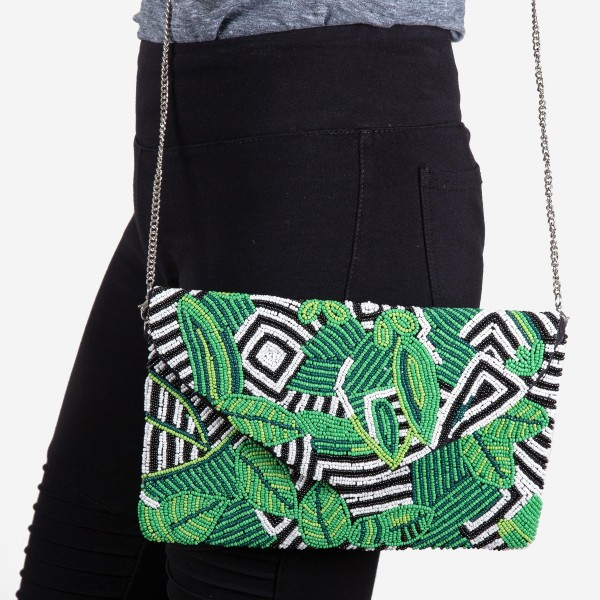 "High quality tropical leaf seed beaded crossbody clutch.  - Open (100% Cotton) lined inside - 1 inside open pocket - Fold over flap snap closure - Approximately 10"" x 7""  - Strap hangs approximately 26"" L - 40% Seed Beads, 40% Cotton Canvas, 20% Metal"