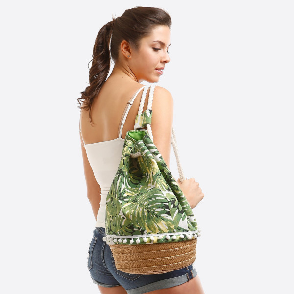 """Fully lined, draw string bag with a tropical print, rope handles that can be worn over one or both shoulders, and an interior pocket. With the round bottom, this bag measures 17"""" in height and 11"""" in diameter."""