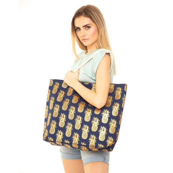 """Navy metallic pineapple canvas beach bag with rope strap details.  - Button closure - One inside open pocket - Approximately 20.5"""" W x 16"""" T  - Strap length 12"""" - 60% Cotton, 40% Polyester"""