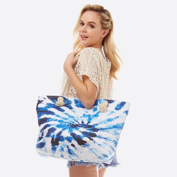 "Blue tie-dye tote bag with rope handles.  - Open inside pocket  - Zipper closure - Rope handles - Approximately 22"" W x 14"" T - Handles 12"" L - 65% Polyester, 35% Cotton"