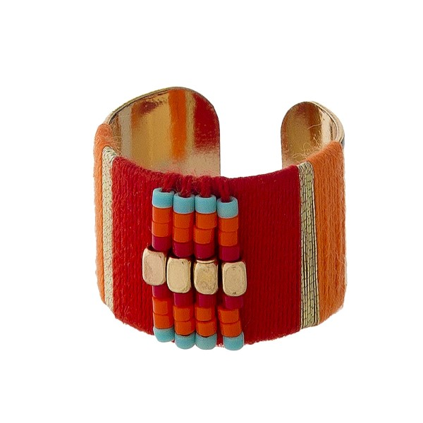 Gold tone ring with red and orange thread wrapping details. Adjustable in size.