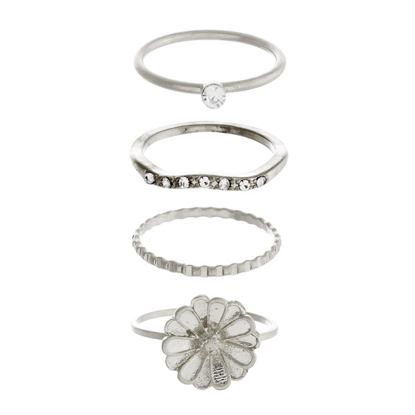 Dainty metal ring set featuring four rings with cubic zirconia details and a flower accent.  - Fits up to a 8 ring size