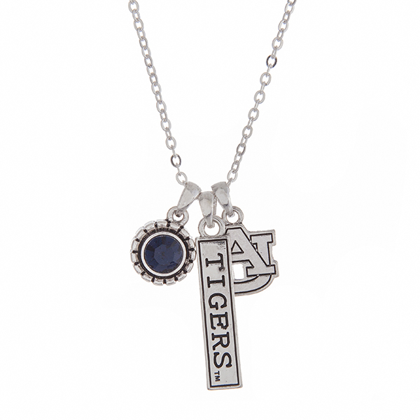 "Officially licensed Auburn University silver tone necklace with a blue rhinestone charm, logo, and a Tigers stamped bar charm. Approximately 18"" in length."