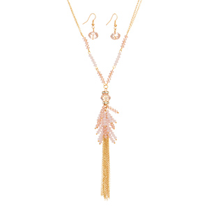 "Gold tone double strand necklace set featuring pink beads with metal tassel accent. Approximately 27"" in length."