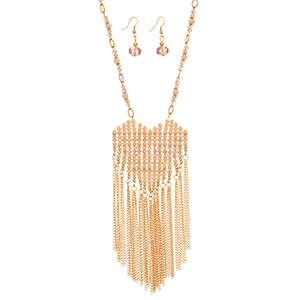 "Gold tone necklace set featuring a ivory and pink beaded heart pendant with metal fringe. Approximately 28"" in length."