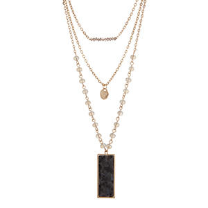 """Gold tone layering necklace displaying gray and white beads, a hammered disk, and a black natural stone pendant. Approximately 23"""" in length."""