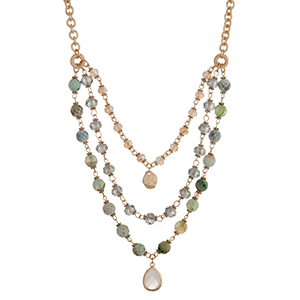 """Gold tone layering necklace displaying mint green beads with a small white teardrop shape cabochon. Approximately 23"""" in length."""
