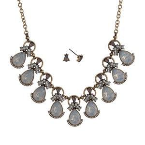 """Worn gold tone necklace set displaying white opal teardrop shape cabochons surrounded by clear rhinestones. Approximately 16"""" in length."""