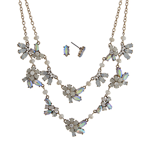 """Worn gold tone layering necklace set displaying ivory flowers with iridescent rhinestone accents. Approximately 20"""" in length."""