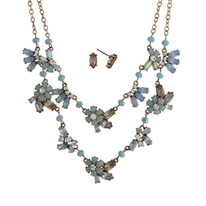 """Worn gold tone layering necklace set displaying mint and blue flowers with clear rhinestone accents. Approximately 20"""" in length."""